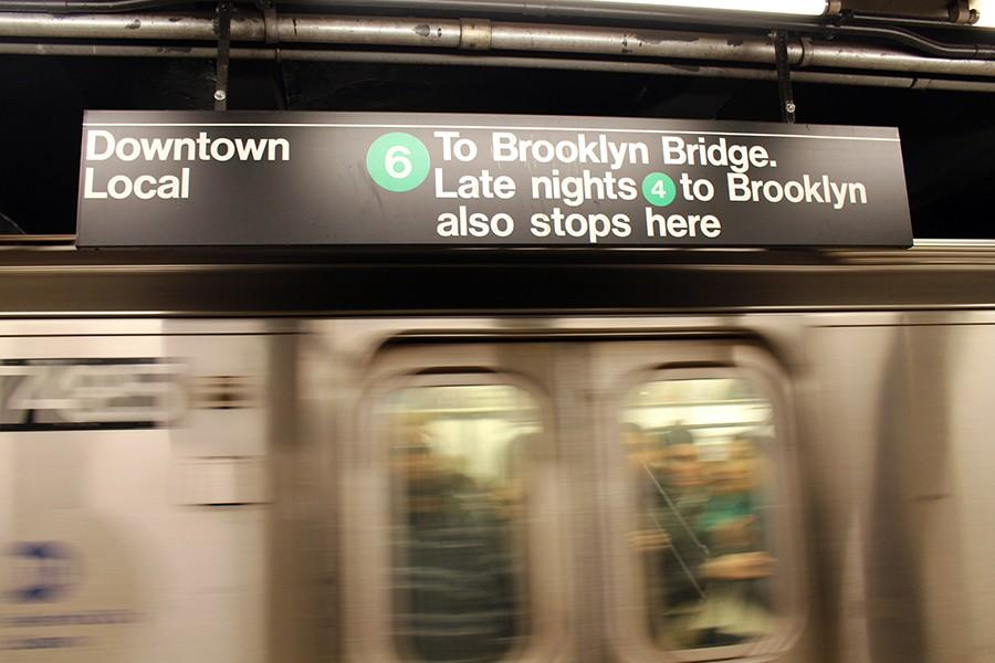 Subway+cars+pass+by+as+the+staff+awaits+the+next+train.+