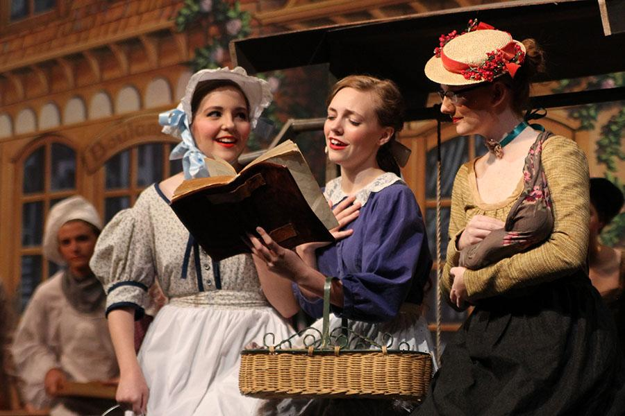 Belle, played by senior Madeleine Farren, shares her love of reading with village women played by sophomore Taryn Glenn and junior Charity Levens.