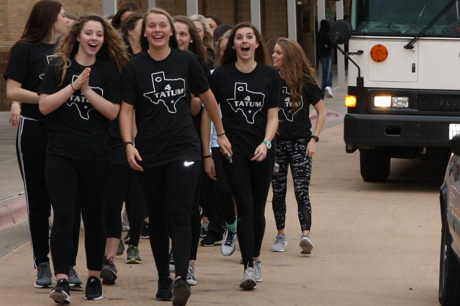 The+girls+basketball+team+walks+down+the+bus+lane+during+the+school+send-off+for+the+state+tournament.