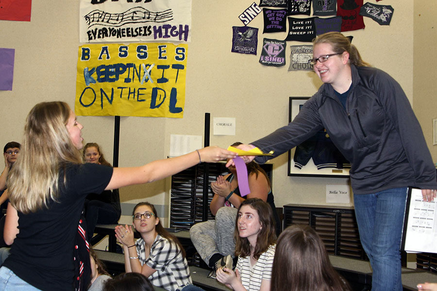 Senior NHS Officer Erica Perez presents Meghan Kempf with the ribbon indication admission to NHS.