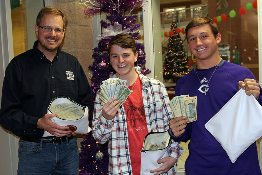 Canyon High STUCO representatives Parker Duggan and Kaden McPherson present $5,231 to High Plains Food Bank excecutive director Zack Wilson.