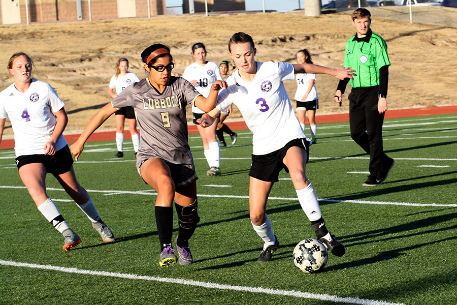 Junior Addison Warren kicks the ball past Lubbock High opponent.