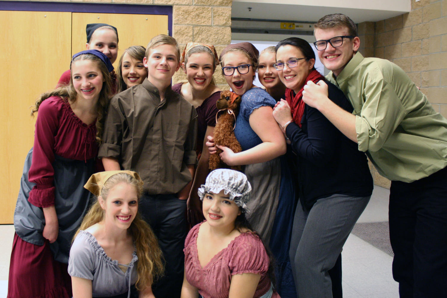 Winterguard celebrates with their mascot, Hugo, after their first showcase.