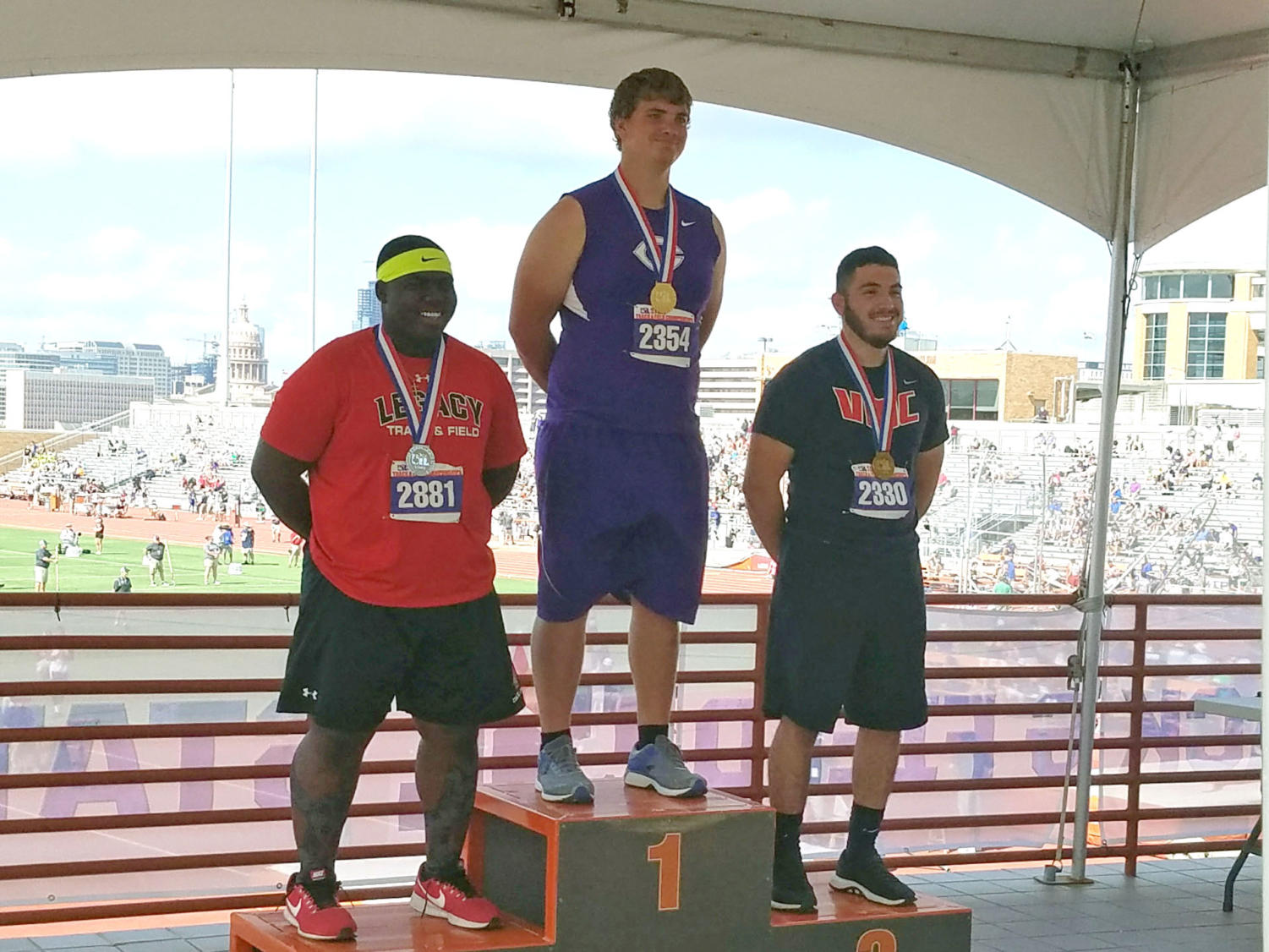 Isaac Huseman receives his first place state medal in shot put at the State UIL Track and Field Meet in Austin.