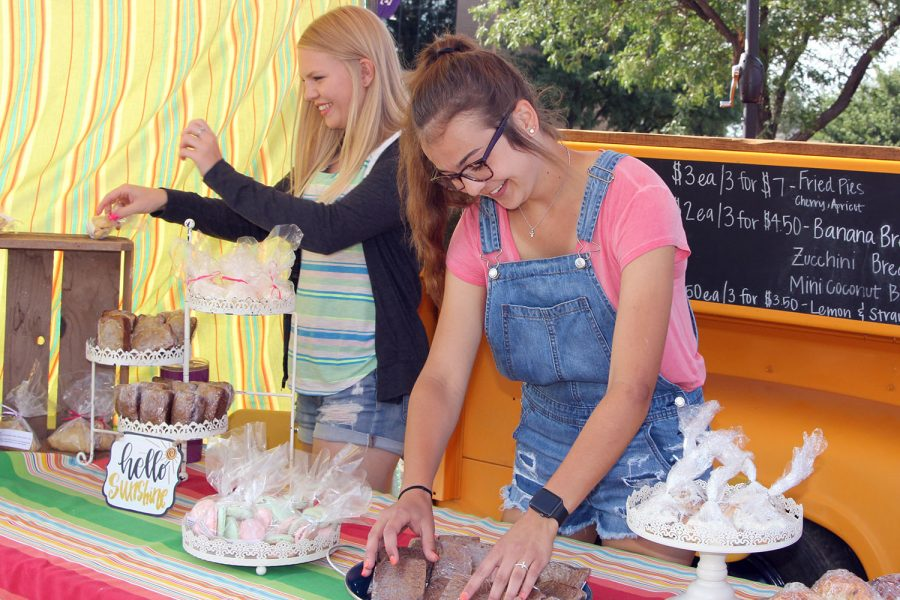 Graduate Emma Irlbeck and senior Maggie Bell arrange baked goods at their farmers market booth Saturday, Aug. 11.