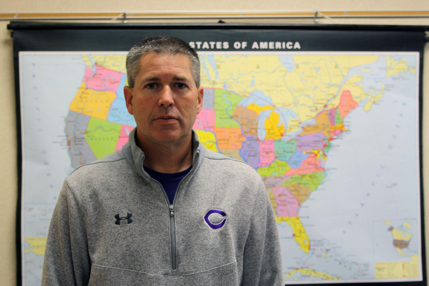Veteran and history teacher Jeremy Chettinger stands in front of a map of the United States.