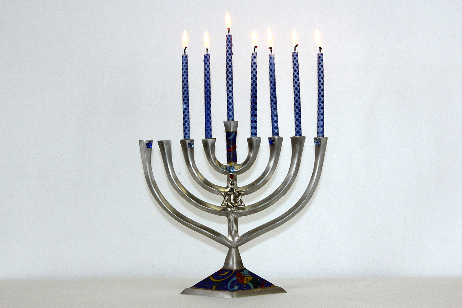 Families celebrate by lighting candles on a menorah throughout Hanukkah.