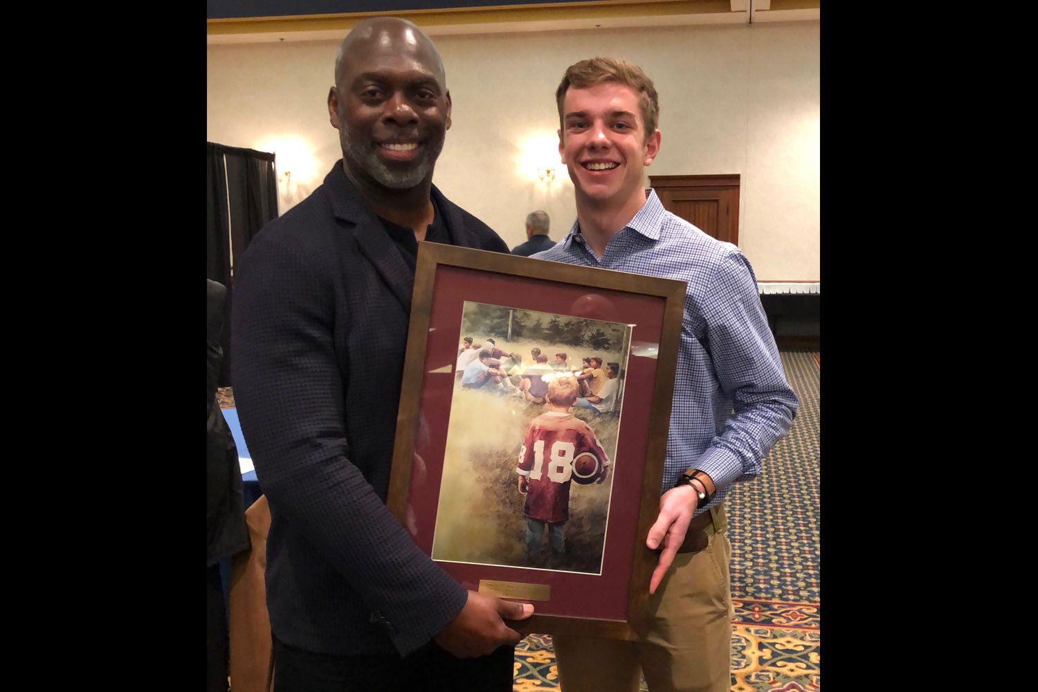 Los Angeles Chargers head coach Anthony Lynn congratulates senior Lawton Rikel at the FCA banquet on Rikel's FCA Male Athlete of the Year award.