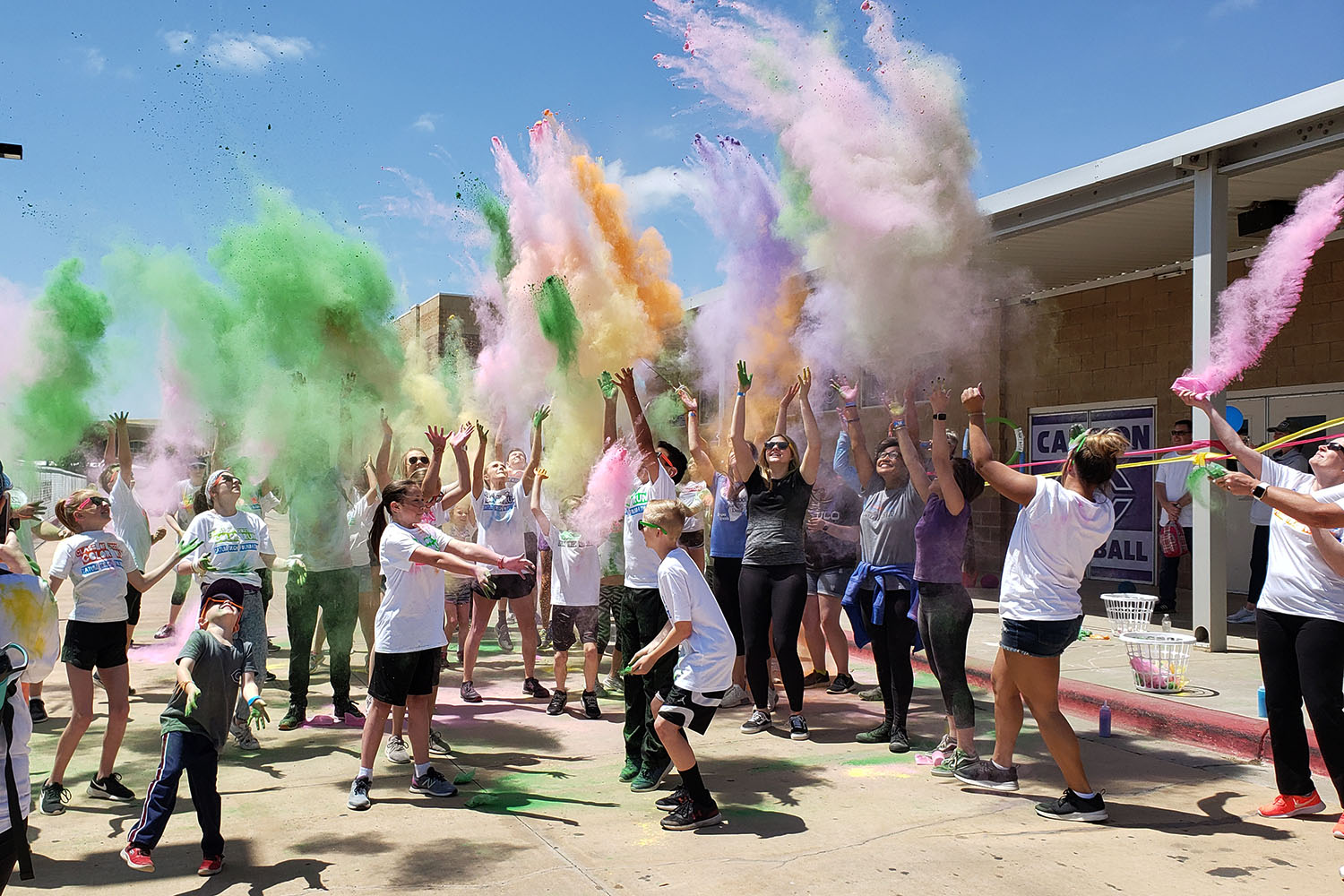 Students throw powder at beginning of the color run fundraiser in support of the Tatum Tough Foundation.