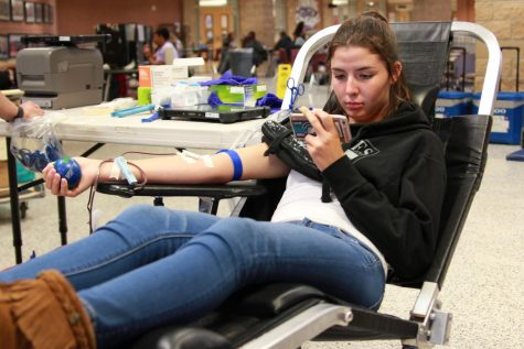 Senior Raven Trevathan watches something on her phone while donating blood during the Vein Drain Blood Drive in October.