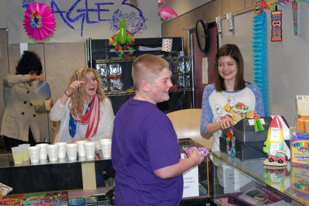 Freshmen Ben Bingham purchases fruit snacks at the Eagles' Nest open house Friday, March 8. Bingham said he shops at the store frequently. Senior Mercedez Flores and juniors Makenna Carson and Amanda Koontz work the open house.