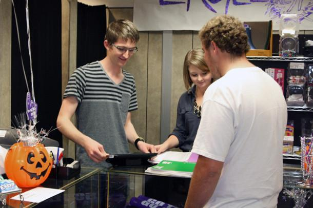 Seniors Logan Hinders and Riley Dunbar process senior Aaron Miller's purchase using the new register system in the Eagle's Nest store.