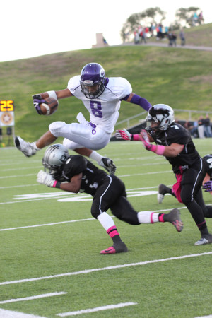Hurdling his opponent, junior Derrick Spencer receives a hand off and attempts to get a first down against Randall.