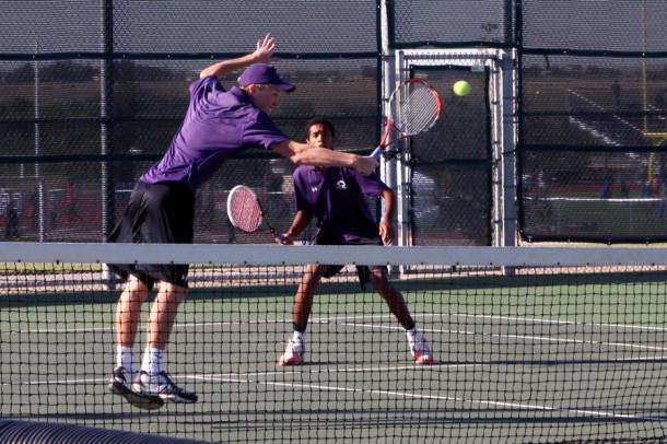 Junior Dylan Strickland stretches across the court for a backhand volley while his doubles partner, senior Sammy Hogan, stands ready in mid-court.