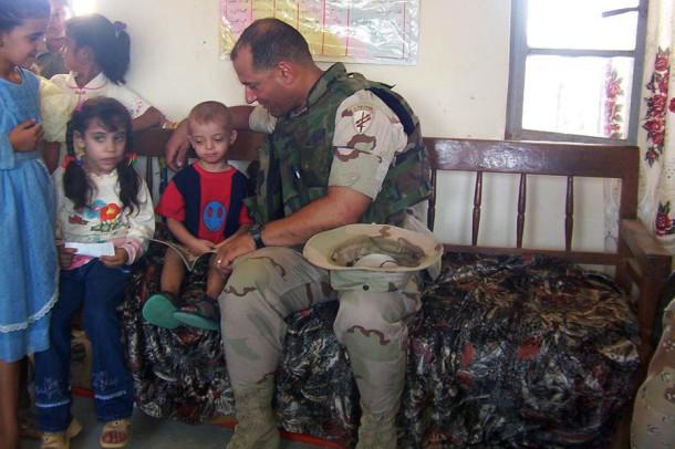 """Luis Hernandez, assistant band director Major Hernandez reads a book in English to an Iraqi child, who told the story back to Hernandez in Farsi, at an elementary school in Diwaniyah, Iraq. """"I really missed my own kids after that day was over,"""" Hernandez said. Hernandez was part of the 413th Civil Affairs Battalion and assessed and rebuilt schools, roads, medical clinics, water treatment facilities and hospitals while in central and southern Iraq. Hernandez served for 24 years in the Army Reserve and is a Veteran of Desert Storm and Iraqi Freedom."""