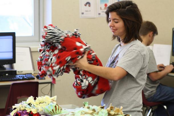 Junior Kassi Price folds and stacks fleece blanks to be sent to the Rainbow Room in Amarillo.