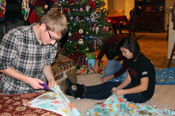 Junior Kendall Tipton cuts strips into a fleece blanket as junior Kassi Price follows behind him tying the strips together at the Key Club Christmas social Dec. 14.