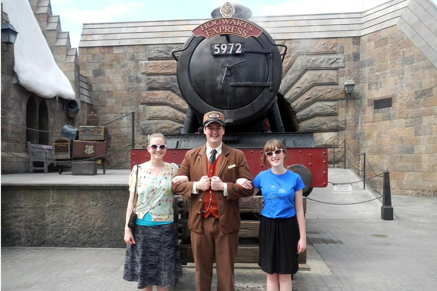 Associate editor Tasha Brown and her cousin Breanna Bassett stand with the Hogwarts Express train conductor at the Wizarding World of Harry Potter in the Universal Studios Islands of Adventure park in Florida.