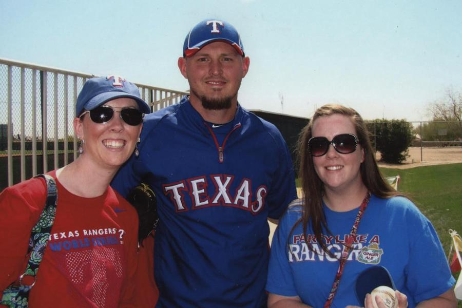 Jessica Ray and her sister, Rachel Huseman, pose with Matt Harrison, a pitcher for the Texas Rangers, at spring training in Arizona.