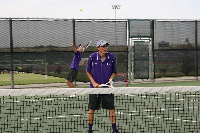 Senior Dylan Strickland serves the ball as senior Brighton McMinn stands ready at the net. The varsity tennis team beat Palo Duro 19-0.