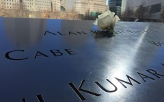 A single rose sits on a name engraved on one of the reflecting pools outside the museum.
