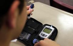Junior Evan Walton checks his blood sugar with a home blood glucose meter. His blood sugar reads