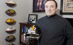 """Walt Evans, former Strength and Conditioning coach for the Pittsburgh Steelers, stands in his Aledo, Texas, home with the football helmet and a picture of himself and former center for the team, Mike Webster, on December 19, 2015. Webster is part of the focus in the upcoming movie """"Concussion,"""" which opens on Christmas Day, and the NFL's handling of Chronic Traumatic Encephalopathy (CTE). (Bob Haynes/Fort Worth Star-Telegram/TNS)"""