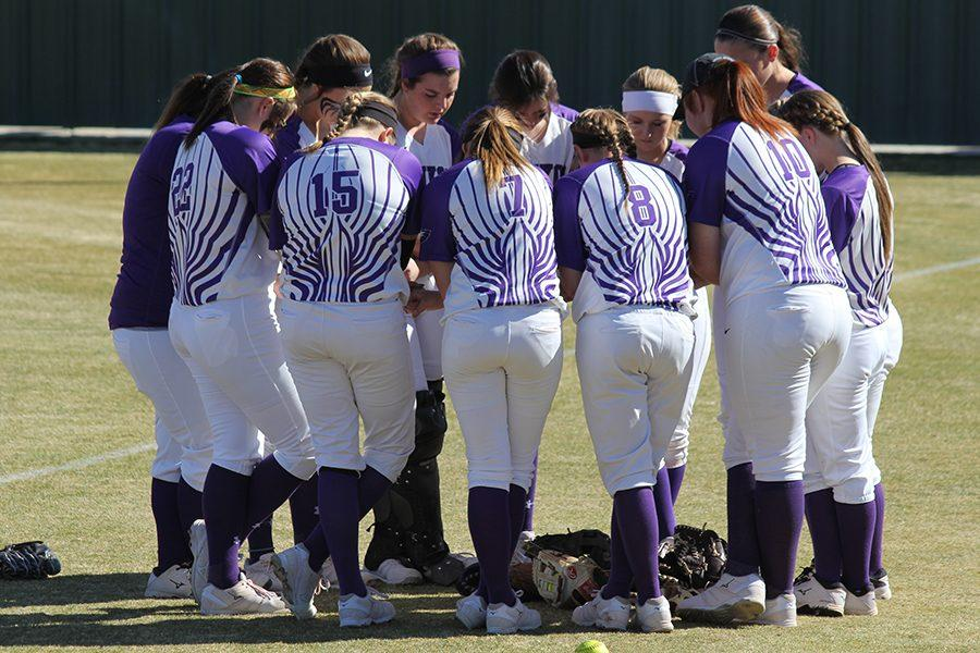 The softball team prays before a Caprock Classic game earlier in the season.