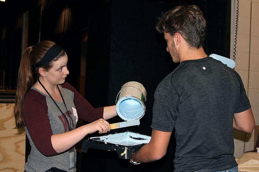 Theater arts teacher Kylie Howell pours paint for junior Brantley Spinks as they work to prepare the set for the upcoming fall musical.