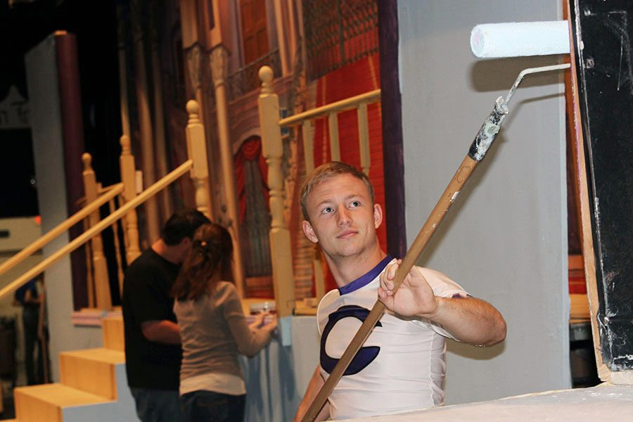 Senior Garrett Brown paints a set piece in preparation for the all-school musical.