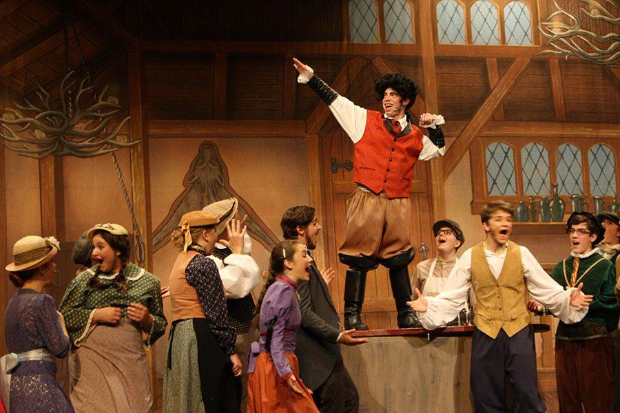 While playing Gaston, junior Josiah Dye flexes on top of a table for the taverne people.