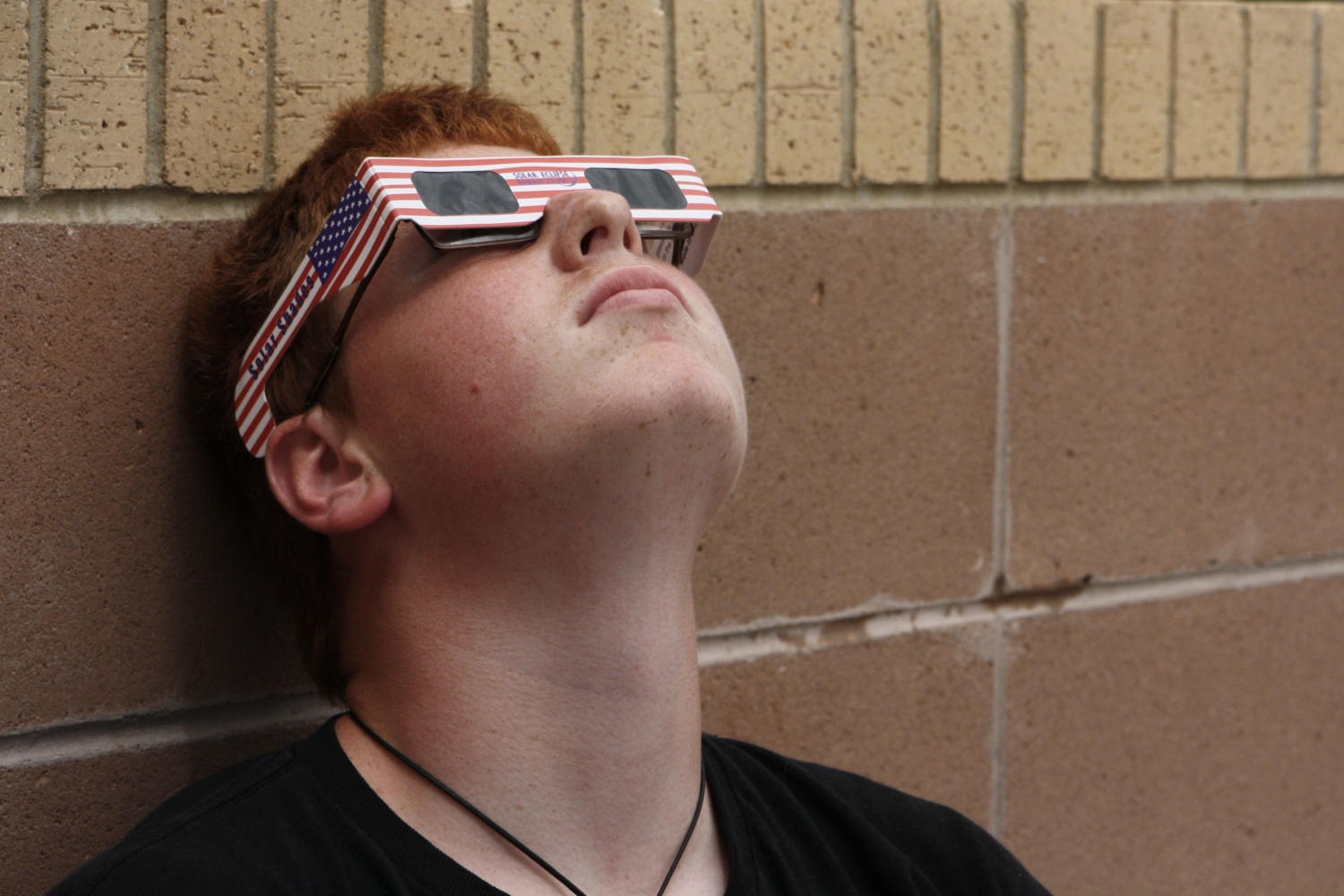 Junior Riley McKown looks at the eclipse through both his prescription and protective glasses.