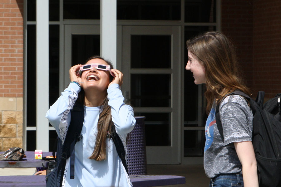 Sophomore Samantha Fernandez reacts to the eclipse with sophomore Erin Bell. Several teachers bought ISO glasses for their students to use during the eclipse.