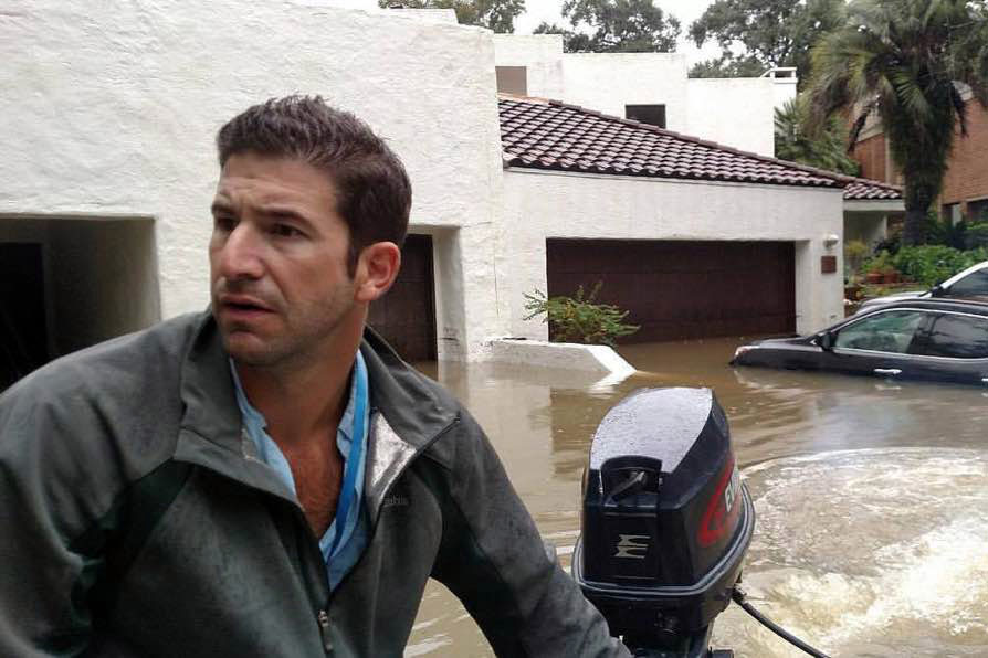 Dr. Lance McClintock uses his boat to navigate flood waters and bring hurricane victims to safety.