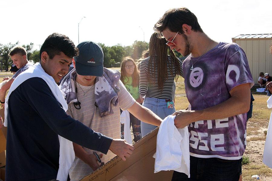 Seniors Aaron Diaz, Parker Duggan and Ethan Stages paint spirit shirts at an after school organizational meeting.