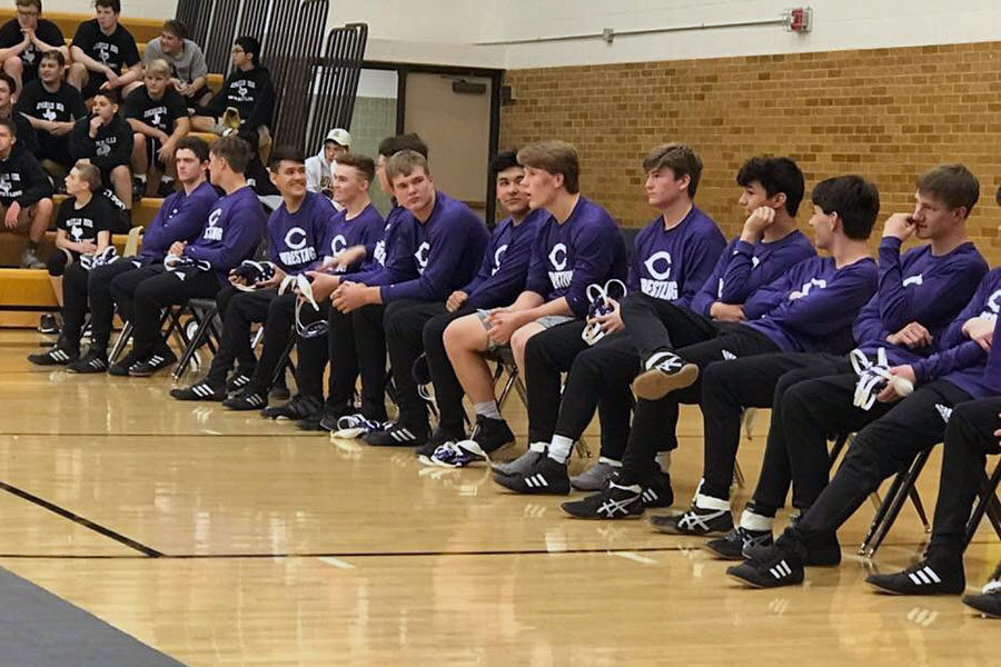 The wrestling team watches one of their teammate's matches at Amarillo High.
