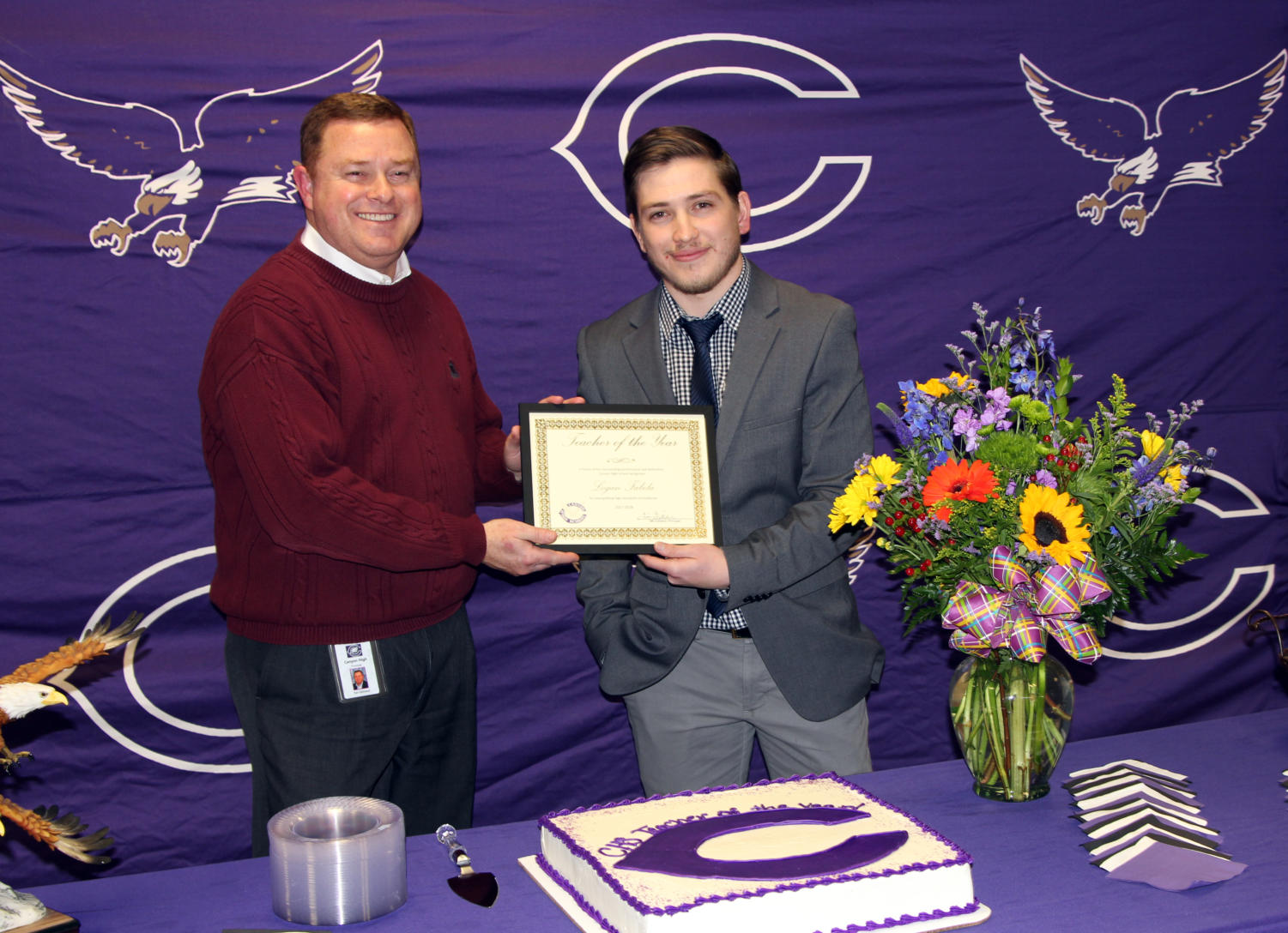 Principal Tim Gilliland awards math teacher Logan Fabela with 'Teacher of the Year'.