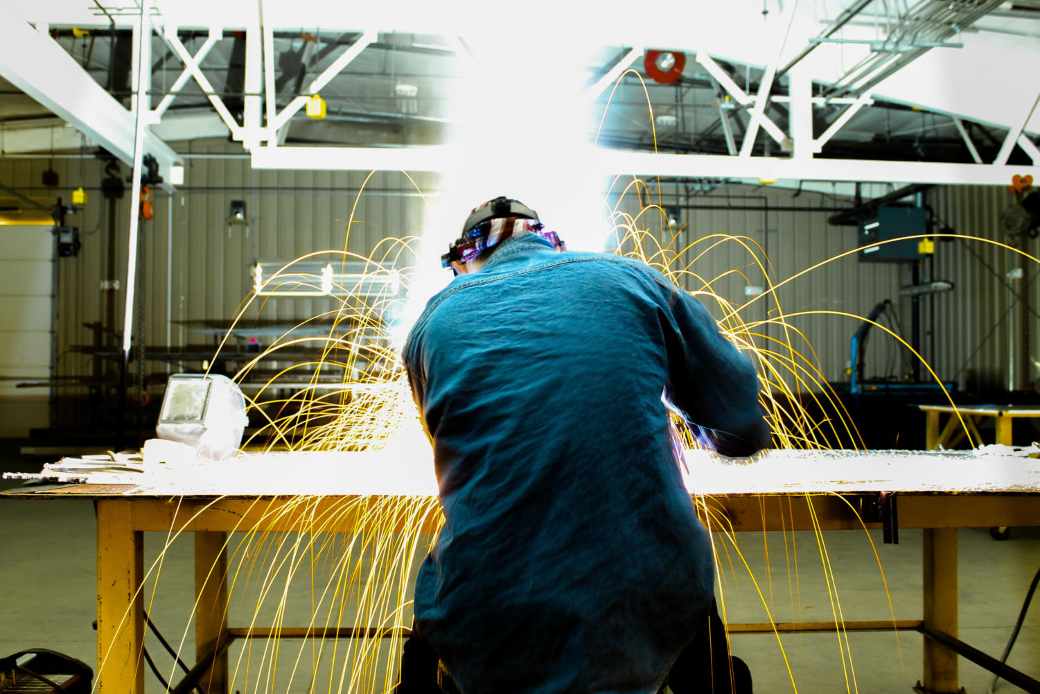 A student in the manufacturing academy welds in class.