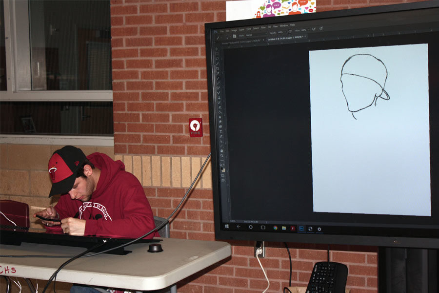 Senior Ethan Stages demonstrates an electronic sketching device at the CHS art table.