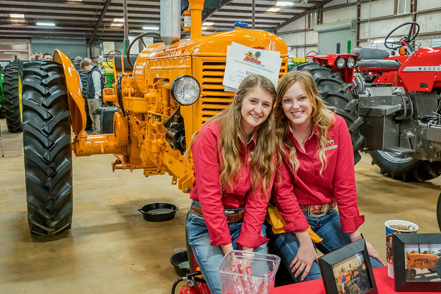 Seniors+Brianna+Ramsay+and+Sarah+Winters+display+the+Minneapolis-Moline+tractor+they+restored.