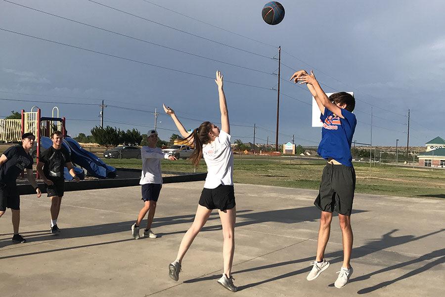 Junior+Myles+Cranmer+shoots+the+ball+as+sophomore+Carter+Cluck+defends+him.