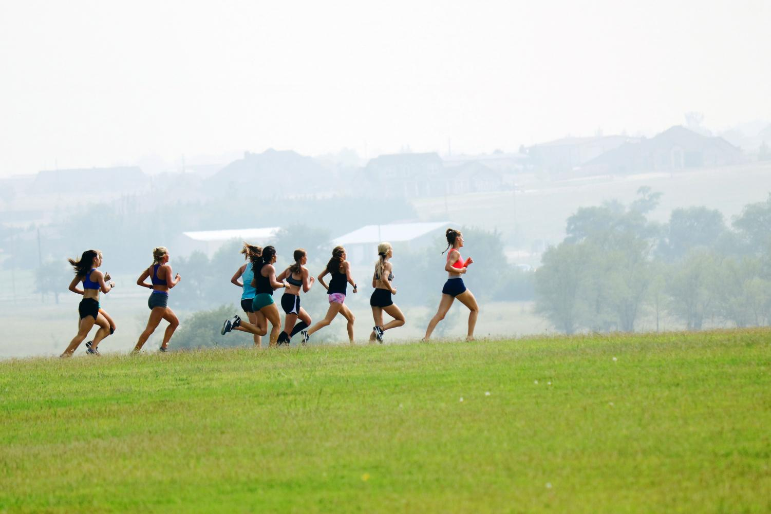 The girls cross country runs through the area behind Canyon High School during a recent workout.