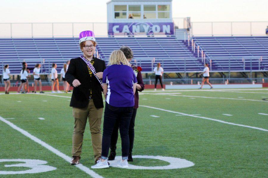 Associate principal Brandi Sanderson places the homecoming king sash on senior Seth Nease.