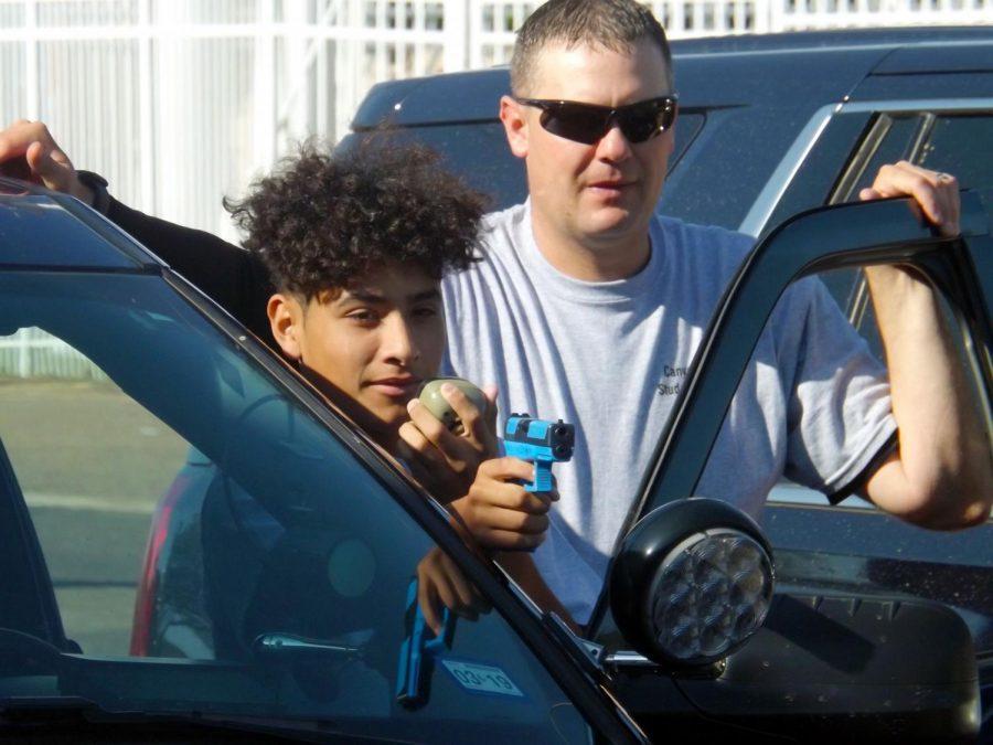 Freshman+Diego+Hernandez+aims+a+gun+with+liaison+officer+Daniel+Roach+during+a+mock+felony+stop.+