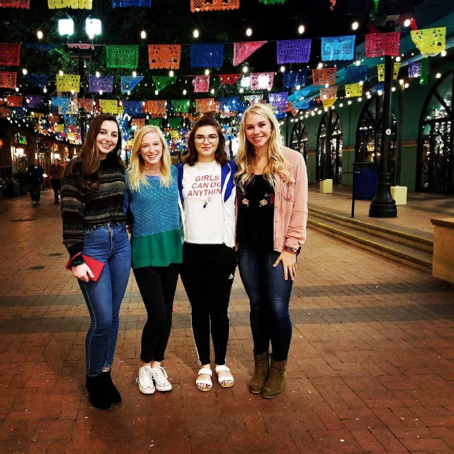 Junior Haley Williams and seniors Katelyn Spivey, Kaylee Buck and Faith Douglass link arms outside the Mi Tierra Cafe.