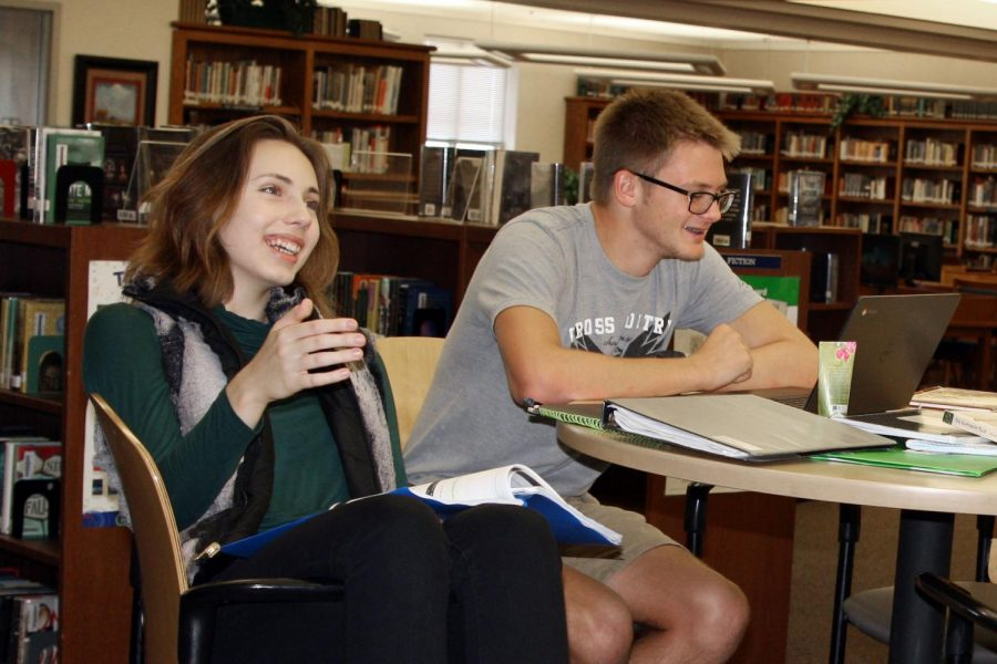 Seniors Erin Sheffield and Wildon Woolley discuss the opening of the CodeBreaker game in the library Oct. 1.