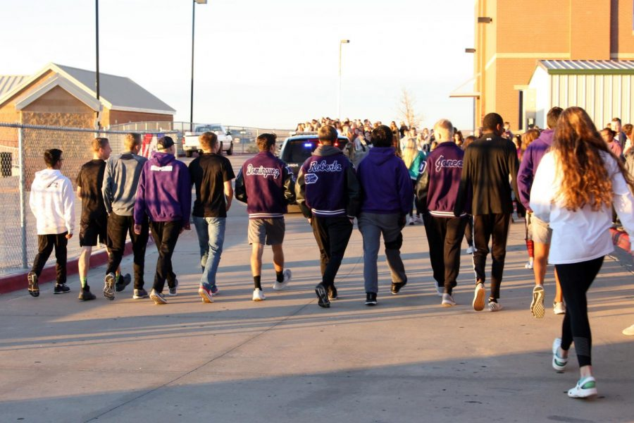 The girls and boys cross country teams leave for the state meet, cheered on by classmates. The boys cross country team is coached by Wesley Kirton.