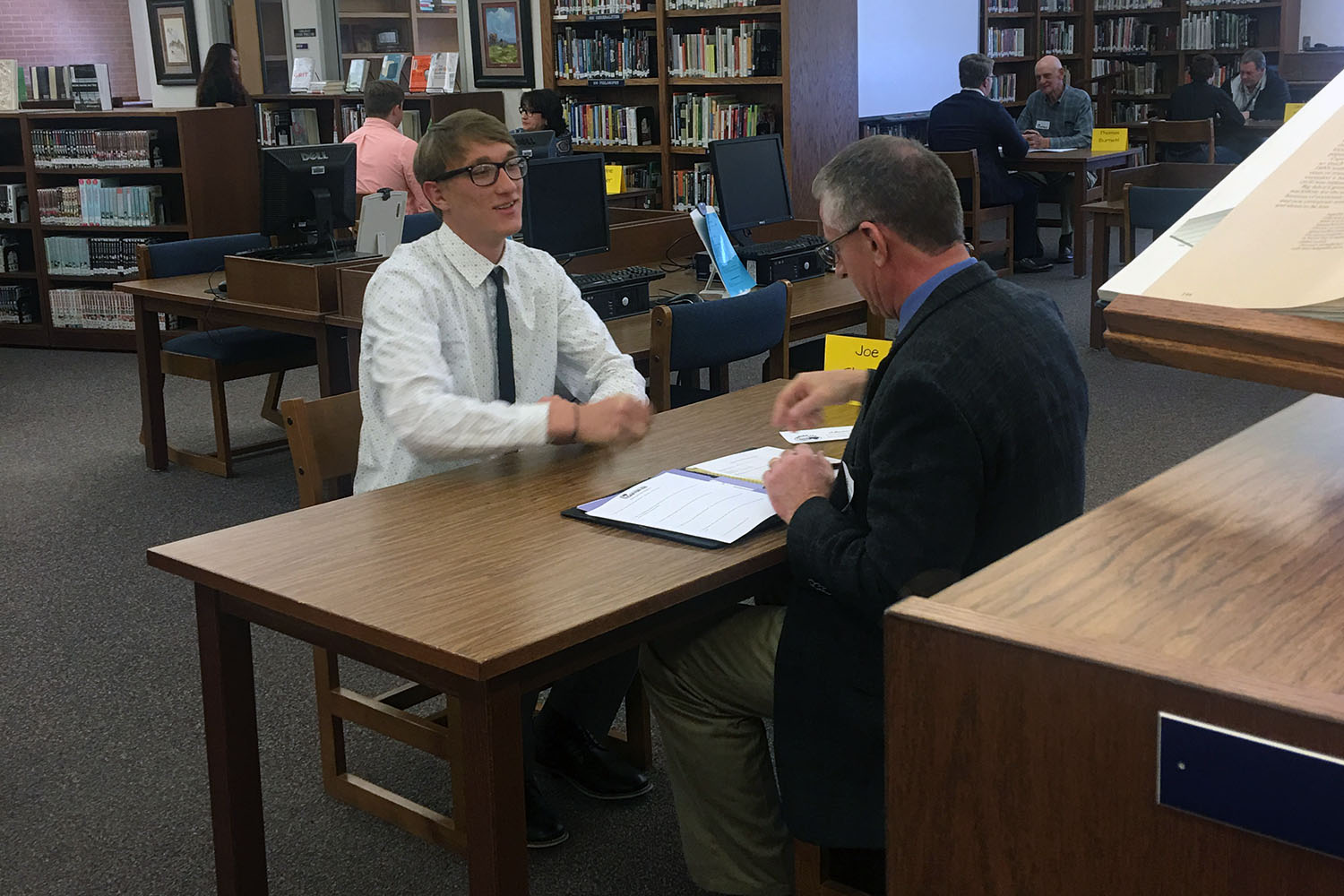 Graduate Miles Kuehn interviews with a community member at last year's Interview Week in the Canyon High library.