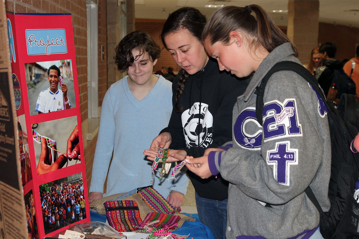 Spanish club members Emily Winters and Carly Behrens show Kelsey Braudt some of the pulseras available for purchase at the Spanish Club's booth during lunch.
