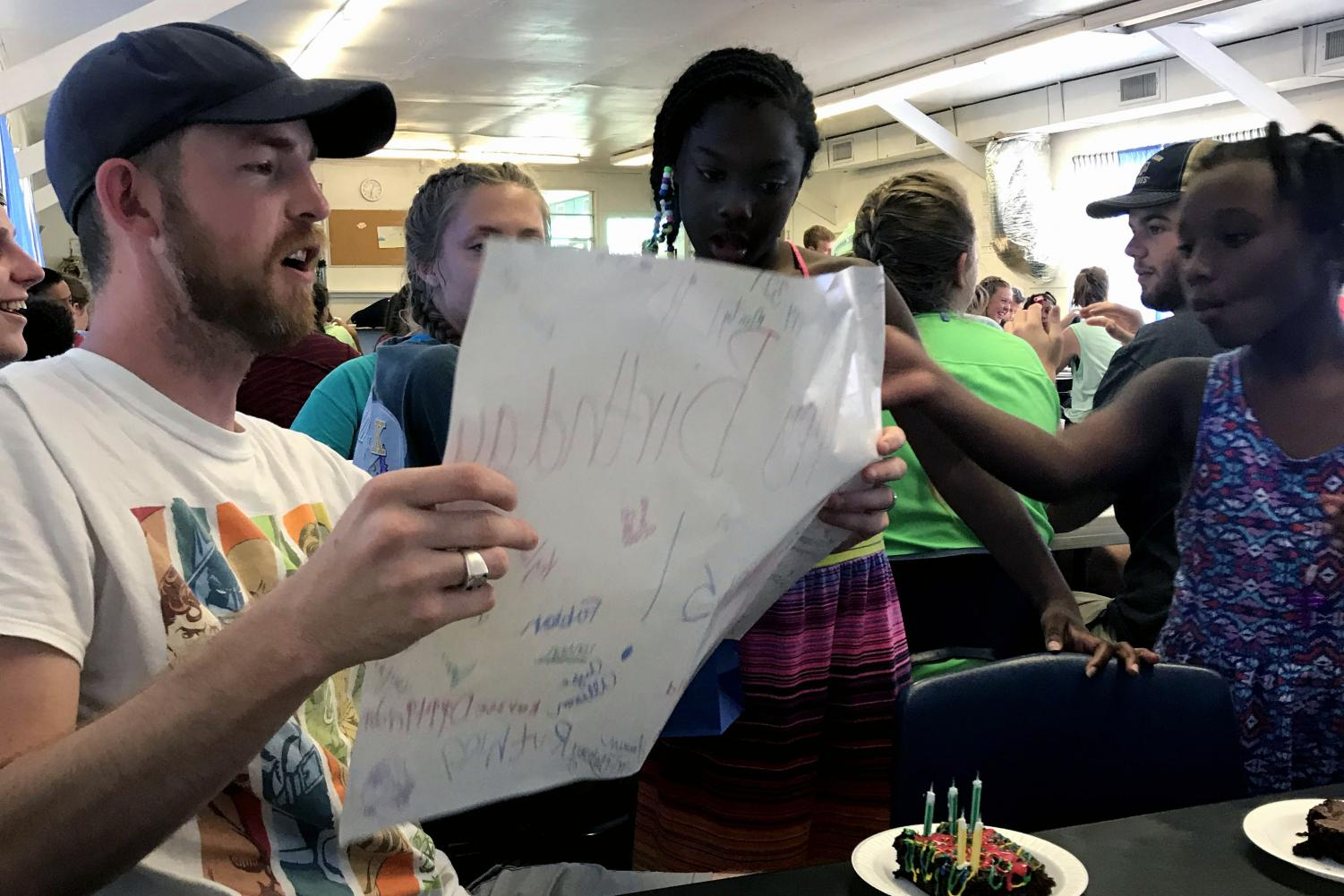 Roberts reads a birthday card students made him during Opportunity Camp, a mission project completed by the University Church of Christ youth group each year.